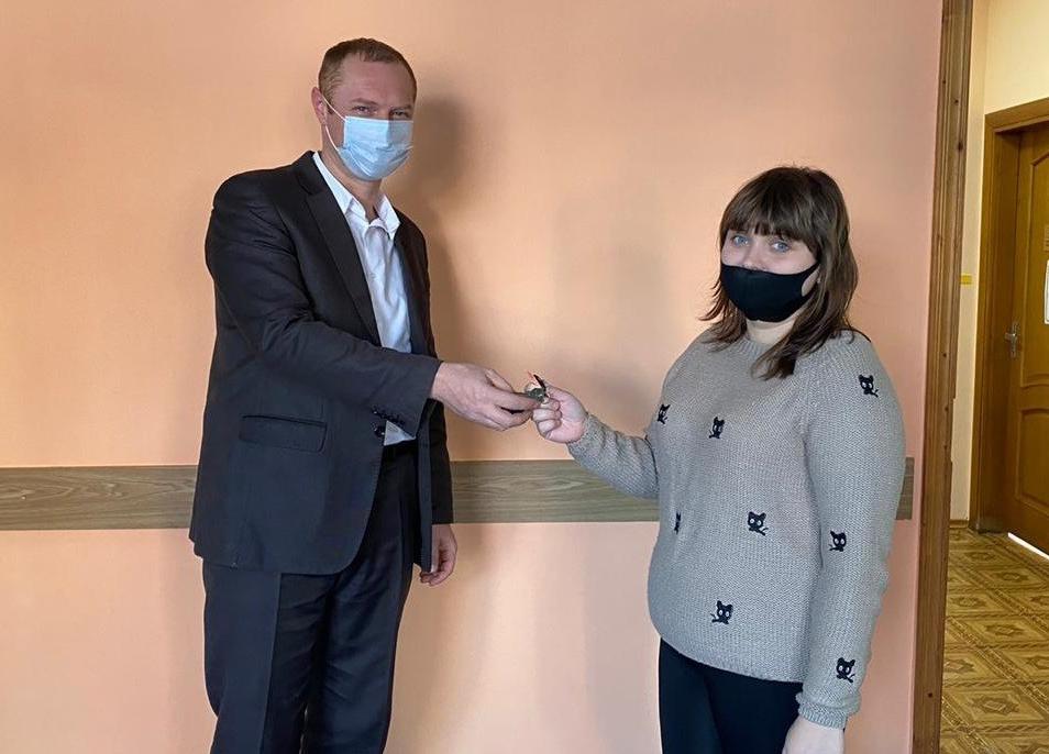 Начальник управления капитального строительства и жилищно-коммунального хозяйства Анатолий Костюк вручает ключи счастливому новосёлу.