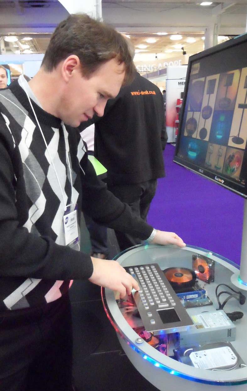 Около одного из стендов. Владимир Вячеславович  знакомится с компьютером. Клавиатура стоит на системном блоке с прозрачной  верхней крышкой, видны все составляющие блоки компьютера.