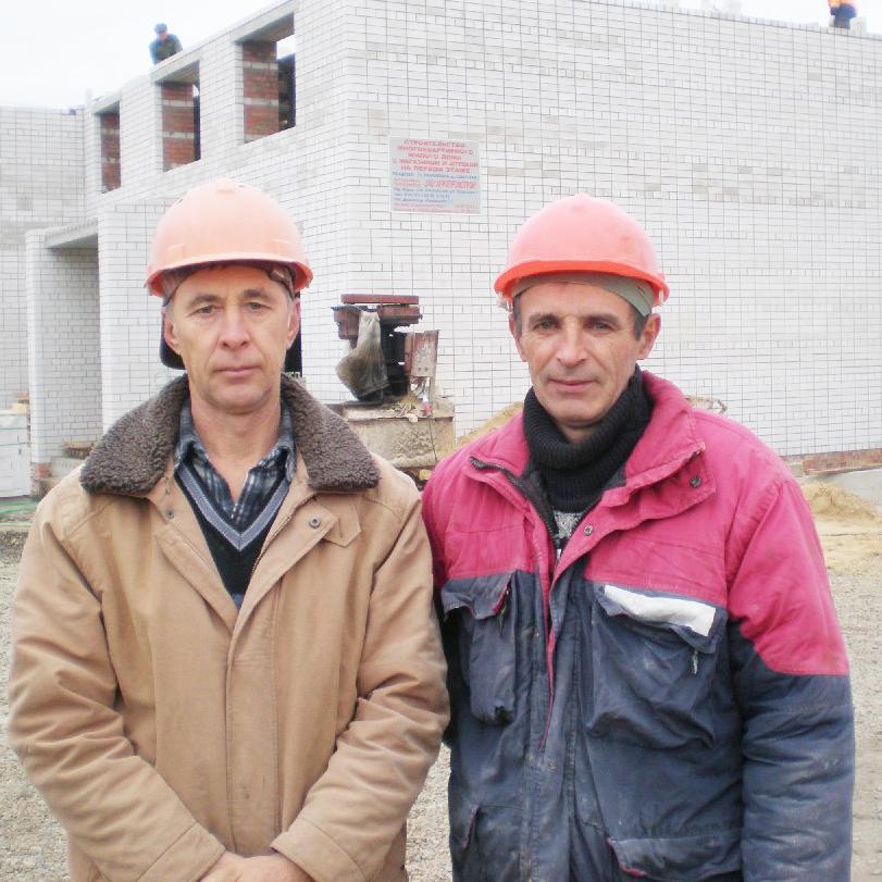 Каменьщики С.Н. Окунев и В.Т. Халёса возводят новый  12-квартирный дом