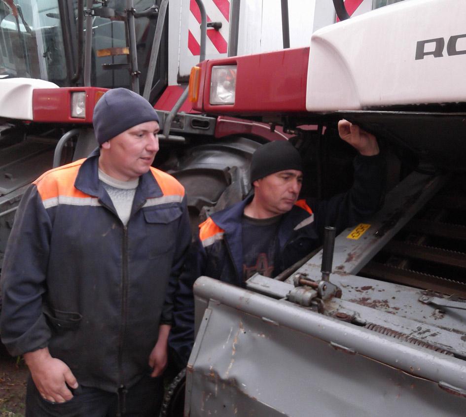 Механизатор Александр Гредчин (слева) и  Игорь Белов проводят профилактический осмотр комбайна «Акрос»
