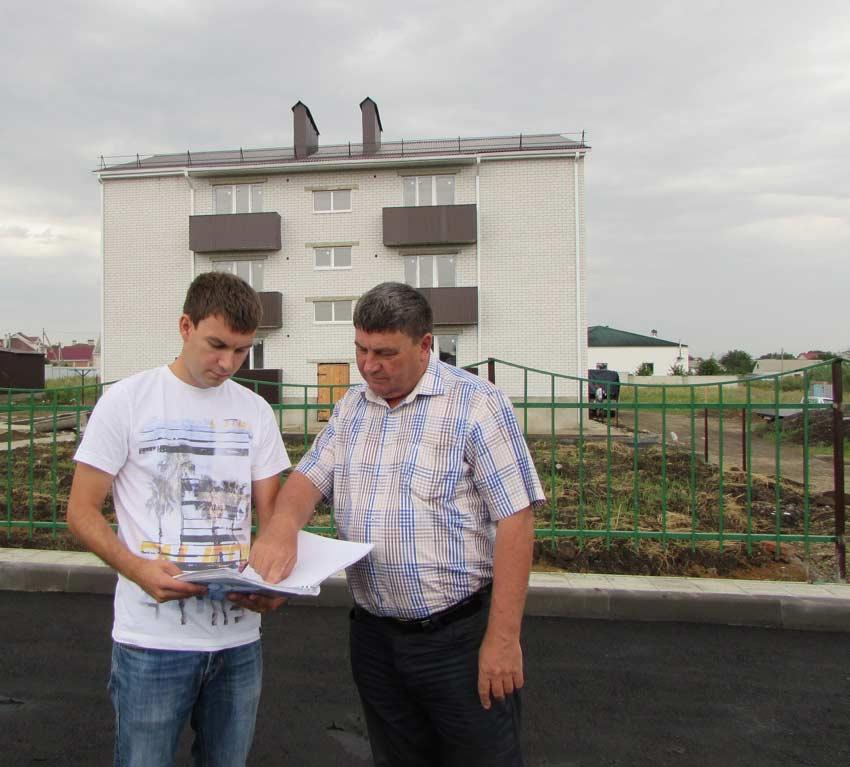 Константин и Иван НиколаевичЯМУШЕВЫ. Позади– возведенный недавно                            12-квартирный жилой дом